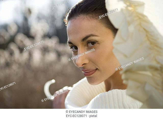 Pretty young woman with a white umbrella in a field