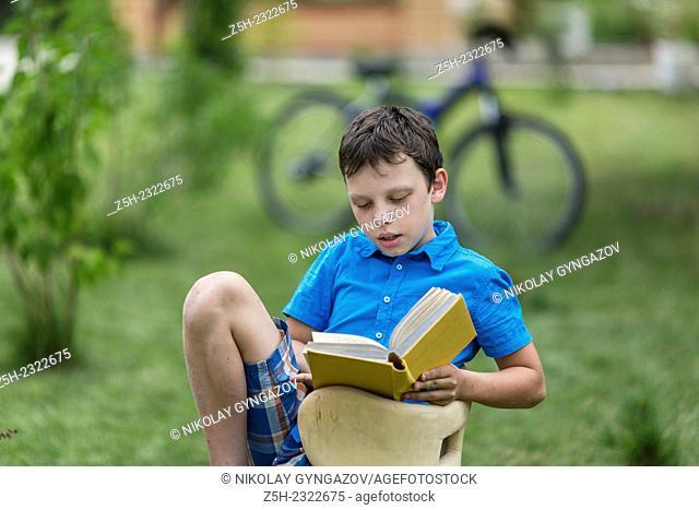 Teen twelve years in the garden with a book