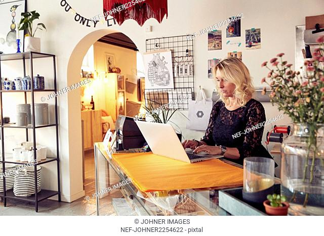 Shop owner using laptop in shop