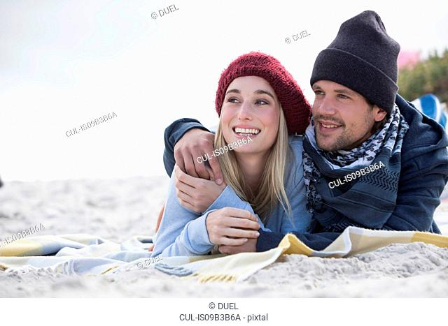 Romantic young couple lying on picnic blanket at beach, Western Cape, South Africa
