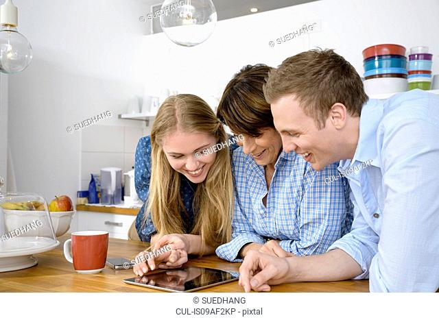Youthful grandmother looking at digital with adult grandchildren