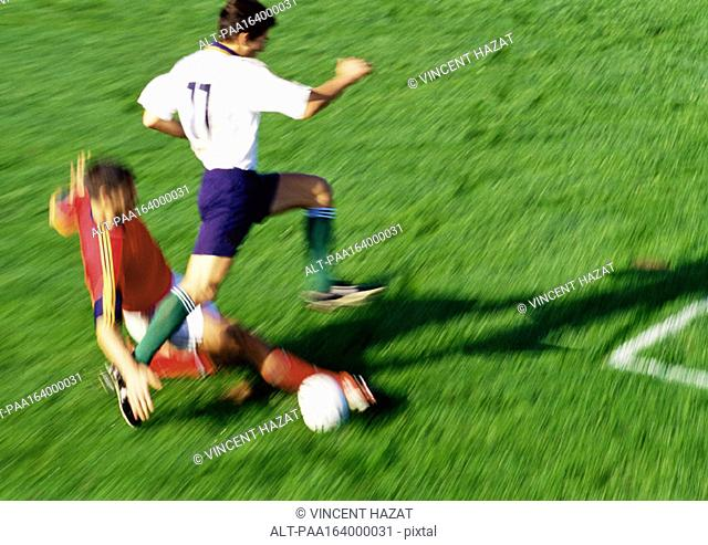 Soccer player reaching for ball, opponent jumping over leg, blurred