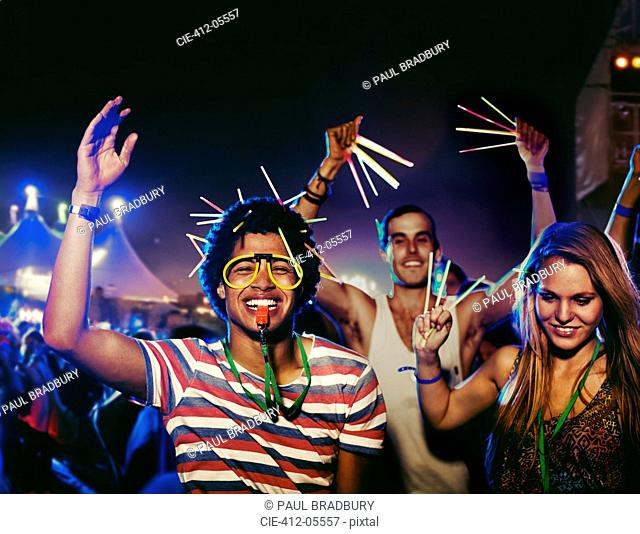 Fans with glow sticks cheering at music festival
