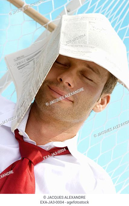 Businessman in hammock with newspaper on head