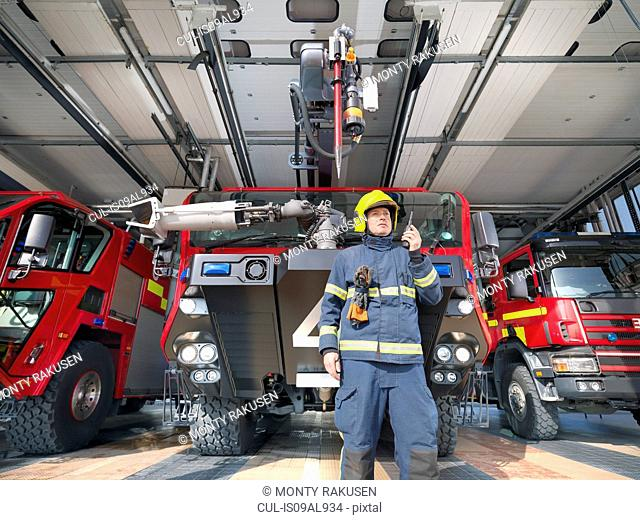 Fireman using walkie talkie in front of fire engines in airport fire station