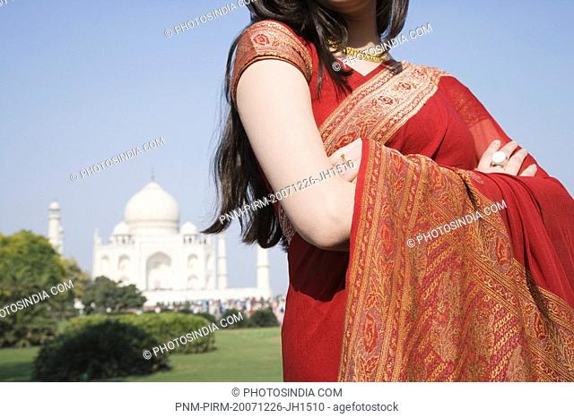 Mid section view of a woman with a mausoleum in the background, Taj Mahal, Agra, Uttar Pradesh, India