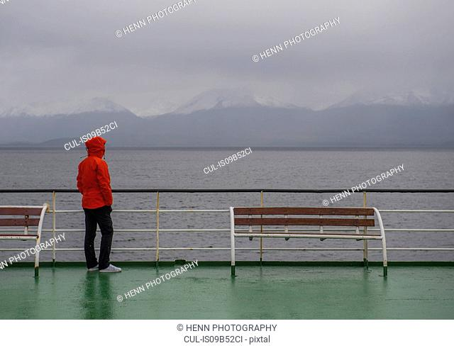 Woman looks out to misty mountains from a ship in the Patagonian fjords, Chile