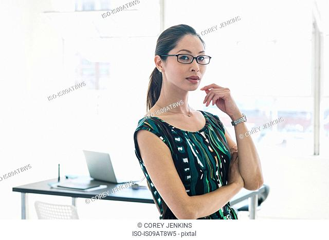 Bespectacled businesswoman in patterned dress by office window