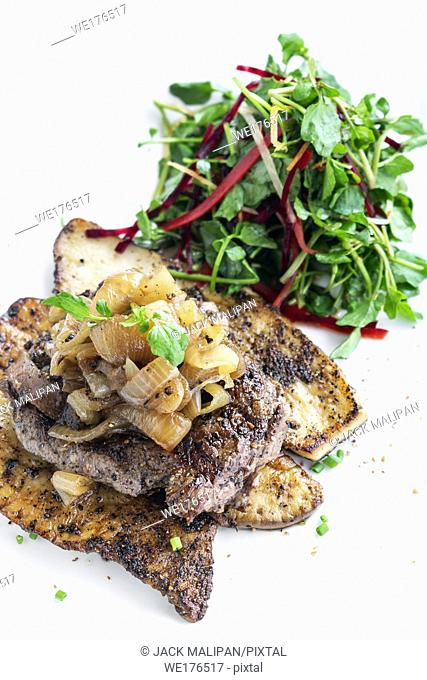 beef steak with grilled mushrooms and caramelized onions gourmet meal on white plate