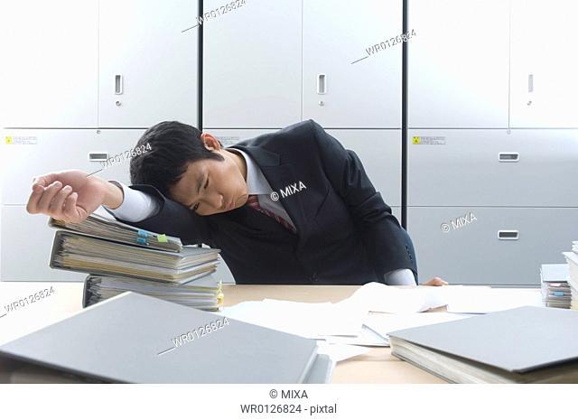 Businessman resting head on files