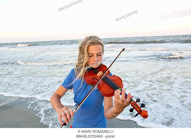 Caucasian girl playing violin at beach