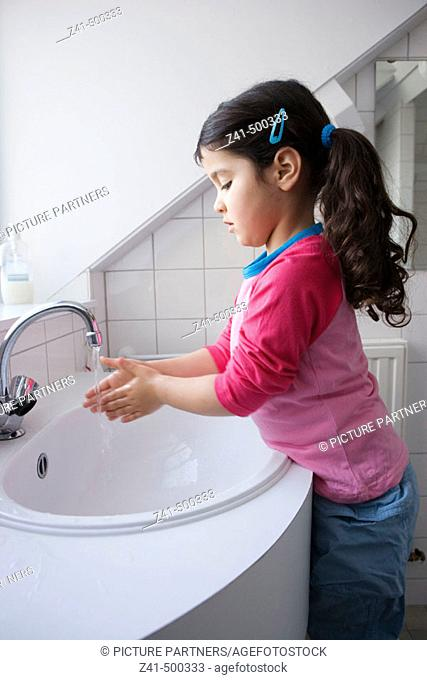 Little girl is washing her hands