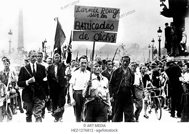 Members of the French Resistance marching through the Place de la Concorde, liberation of Paris, August 1944. The placard reads: The Red Army on the Barricades...