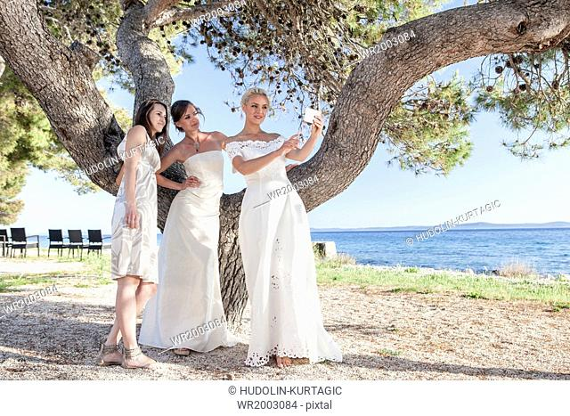 Bride and bridesmaids taking photo of themselves