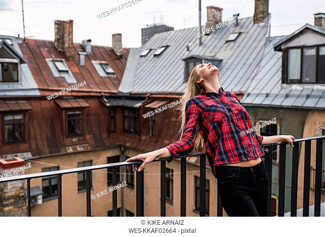 Smiling young woman standing on balcony looking up
