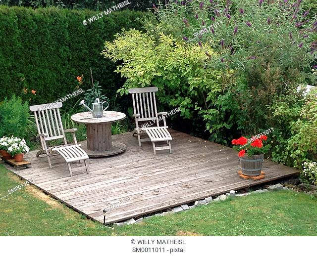 sundeck with teak deck chairs and tabel in garden