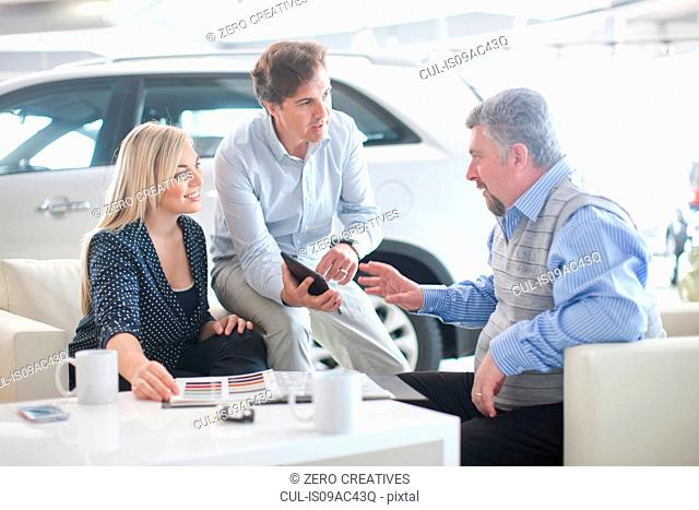 Car salesman talking to couple in car showroom