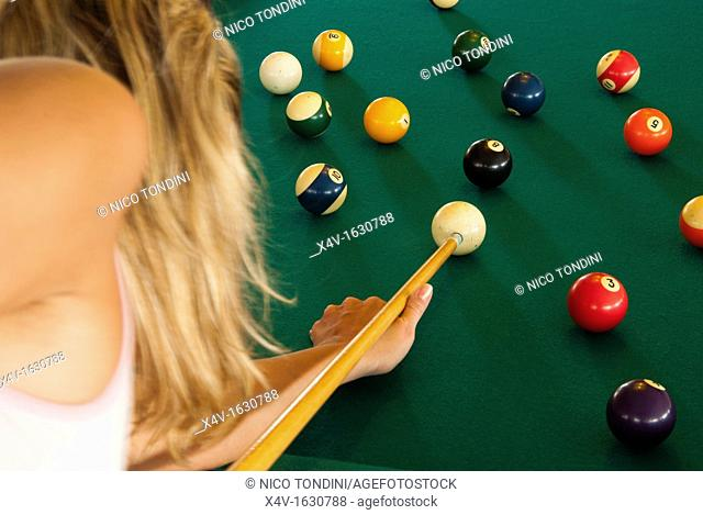 Woman sizing up a shot at pool table, Phuket, Thailand, Southeast Asia, Asia