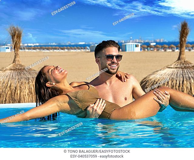 Tourist couple bath in infinity pool on a beach resort in summer vacation