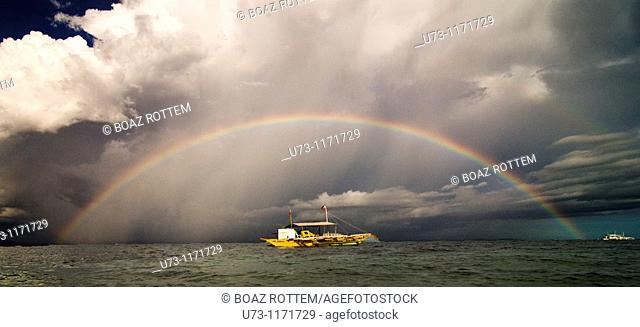 A beautiful full size rainbow on a stormy day in The Philippines