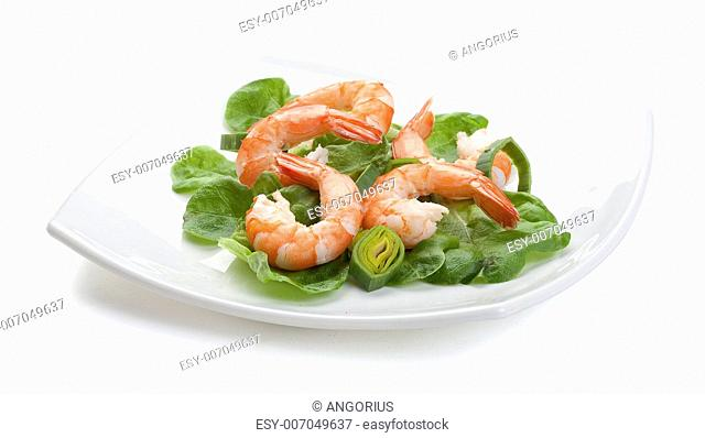 Some shrimp's tails with fresh leek and lettuce on the white plate