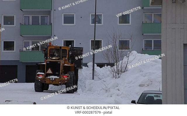 A wheel loader is clearing a courtyard on a gray winter day. Timra, Västernorrlands Län, Sweden