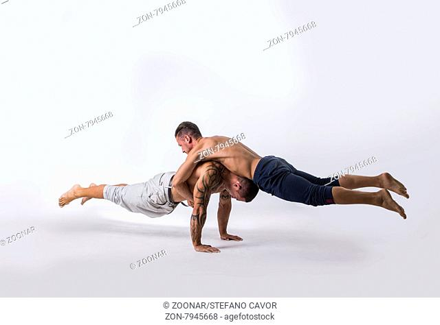Muscular Shirtless Male Acrobatic Dancers Balancing on Top of Each Other in Studio with White Background