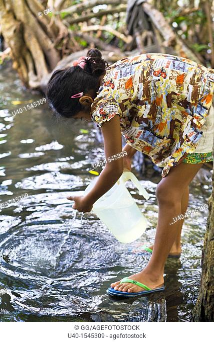 Guatemala, Rio Dulce, girl getting water from River