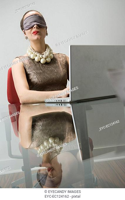 Young woman wearing eye mask, using laptop and contemplating