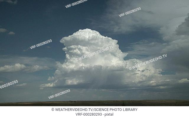 Timelapse footage of the growing anvil of a cumulonimbus thundercloud. A bright shaft of hail is visible below the cloud
