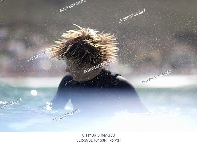 Teenage surfer shaking his hair