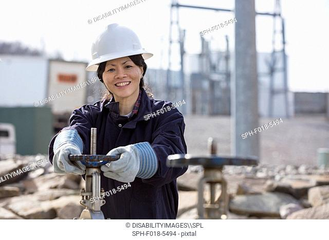 Female power engineer adjusting water valves at power plant