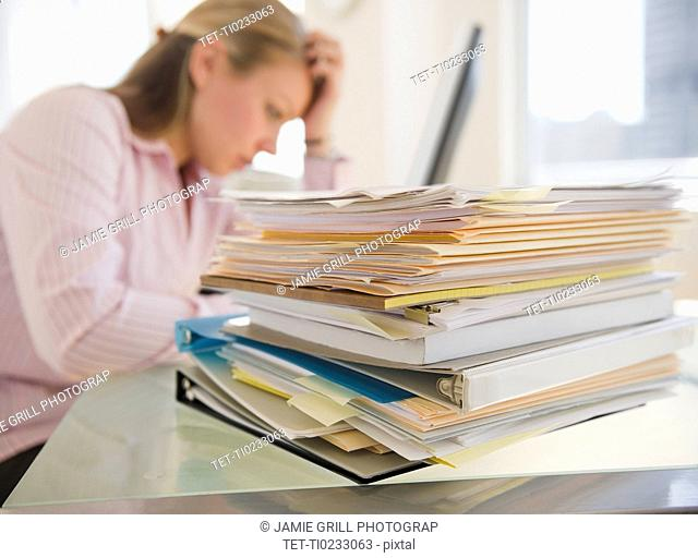 USA, New Jersey, Jersey City, Stressed young businesswoman doing paperwork