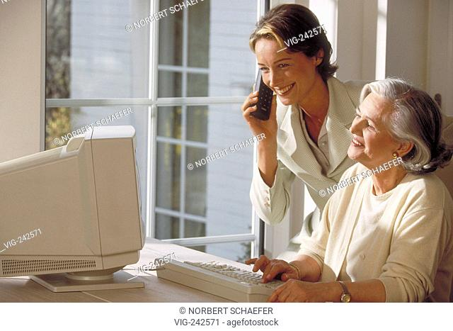 indoor, ca. 30-year-old woman stands beside her mother sitting at the table near the window at the computer making a phone call  - GERMANY, 04/03/2005