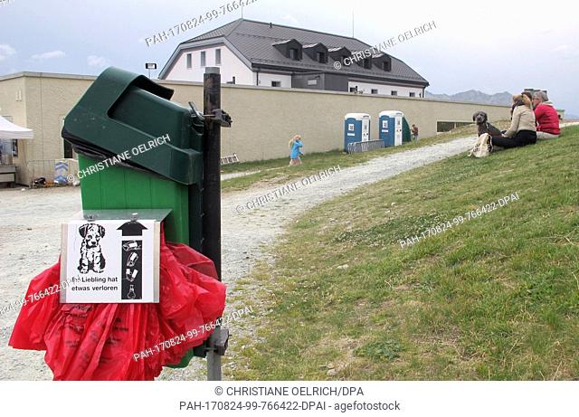 Picture of a dog toliet, bags for dog droppings and a trash can, taken in Muottas Muragl - a good 2500 meters high - in the canton of Graubunden, Switzerland