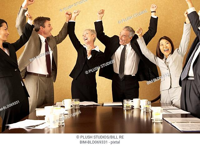 Group of businesspeople cheering at conference table