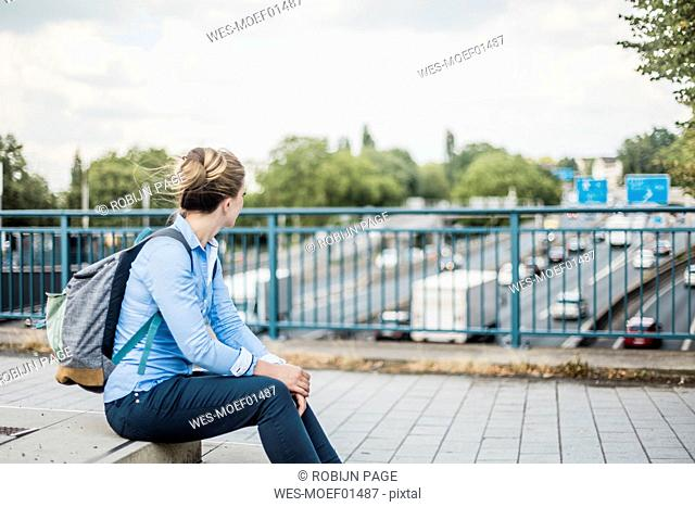 Woman with backpack sitting on motorway bridge