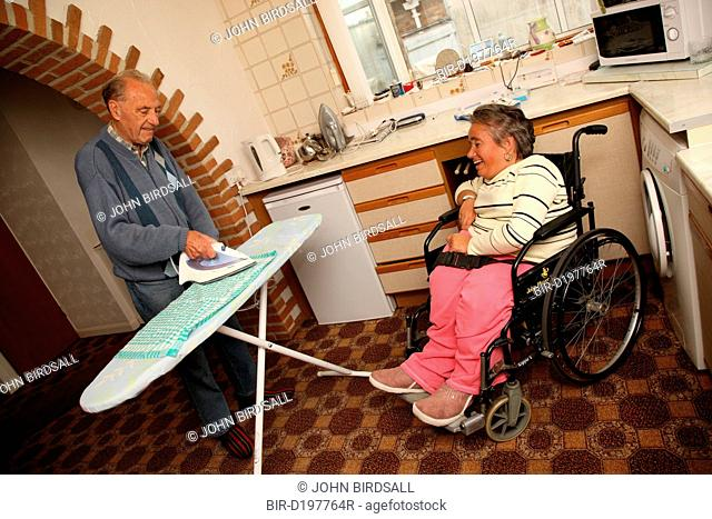 Wheelchair user with Spina Bifida watching her father do ironing