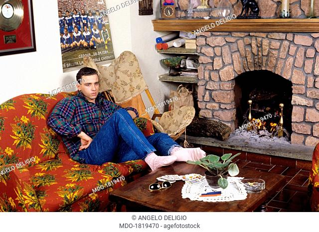 Italian singer-songwriter Eros Ramazzotti sitting thoughtful on a sofa resting his feet on a wooden coffee table. Italy, 1986