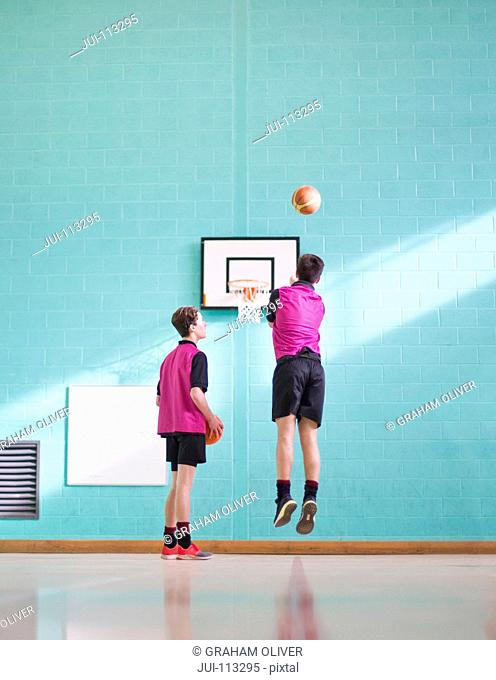 High school students playing basketball in gym class