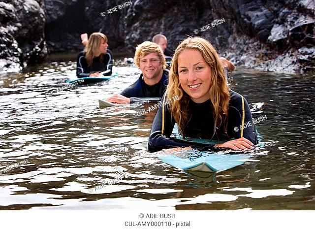 Four people lying on surfboards in the water smiling