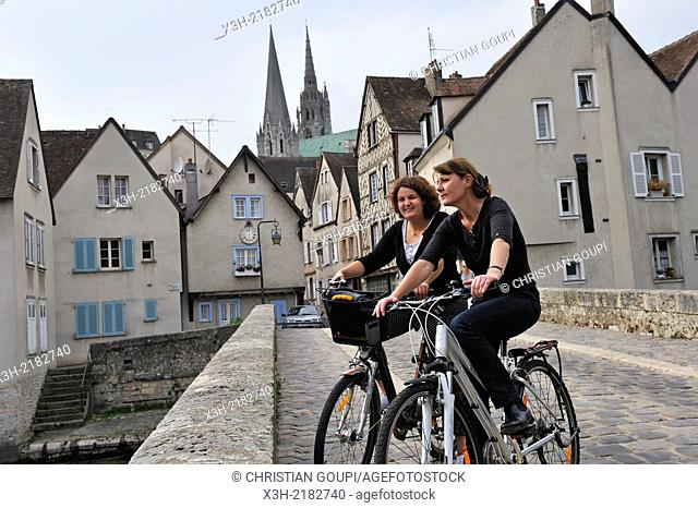 young women cycling on the Bouju bridge and Bourg street with the Cathedral of Chartres background, Chartres, Eure & Loir department, region Centre, France