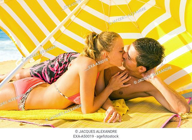 A beautiful couple kissing under a sunshade on a beach