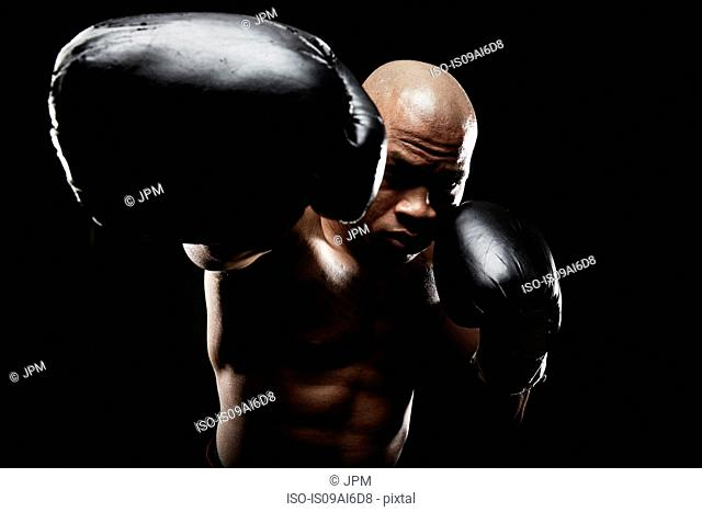 Boxer with black boxing gloves punching towards camera