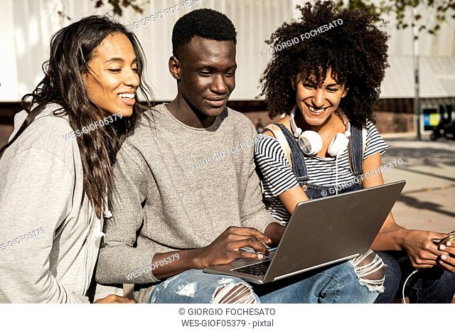 Friends sitting on a bench in the city, having fun, using laptop