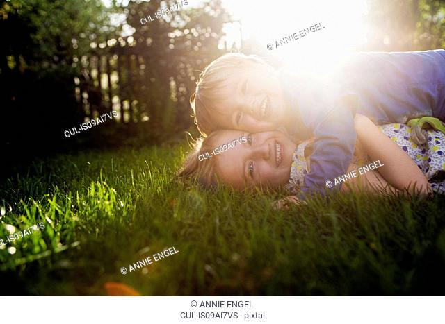 Brother and sister lying on grass, hugging