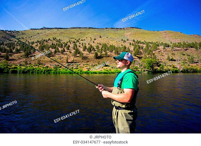 Experienced fly fisherman fishing the Deschutes River in Oregon, casting for fish while standing in the water