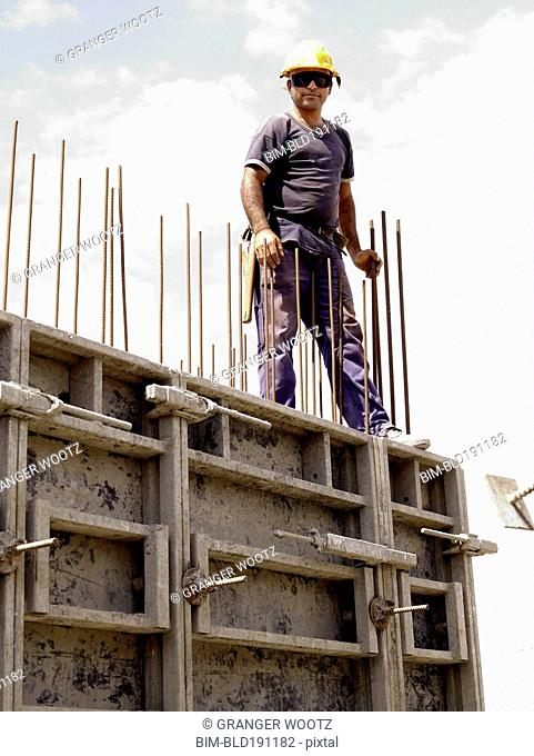 Hispanic worker standing on top of wall on construction site