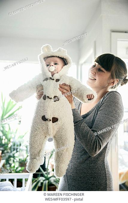 Mother holding up baby in a polar bear costume