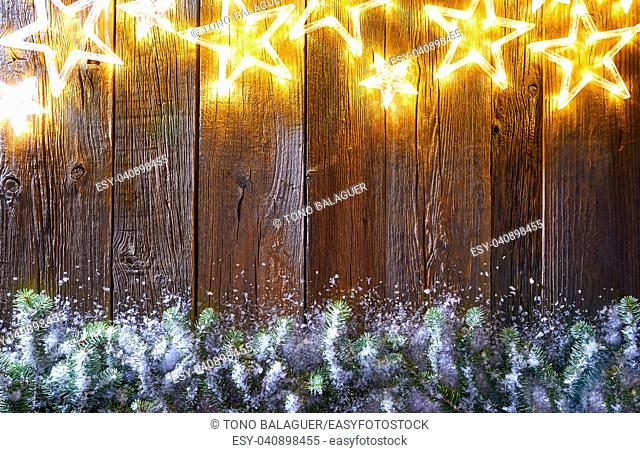Christmas glowing stars and snow fir on vintage wooden background copy space